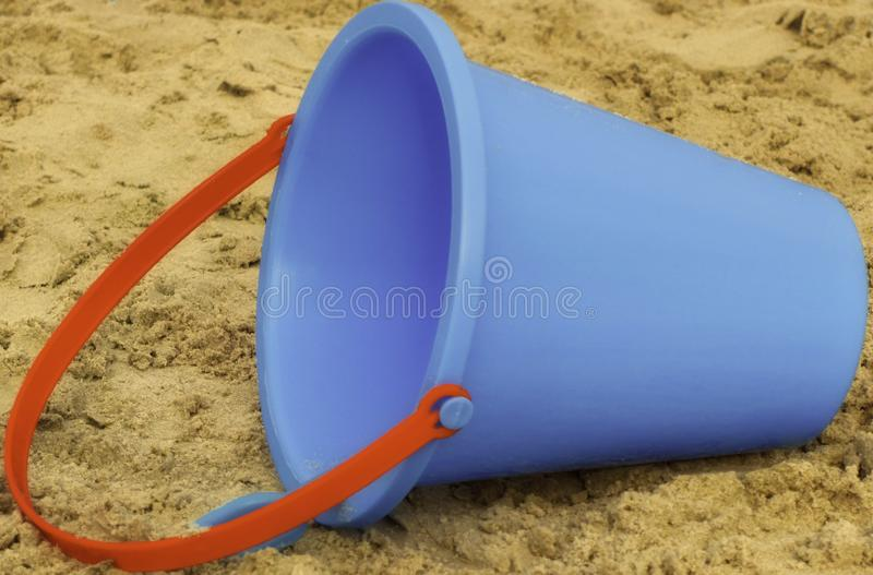 Secchio blu della sabbia con la maniglia rossa, giocattolo della spiaggia dei bambini fotografia stock