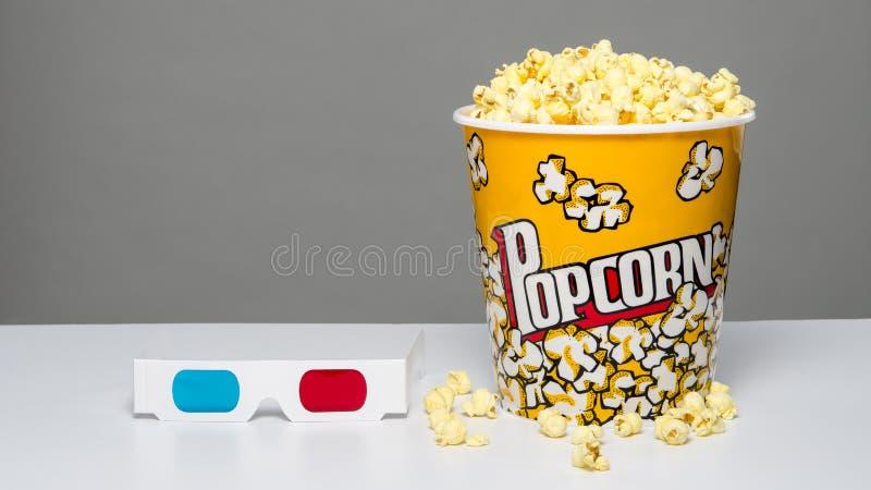 Secchio del popcorn con i noccioli ed i vetri 3d immagine stock libera da diritti