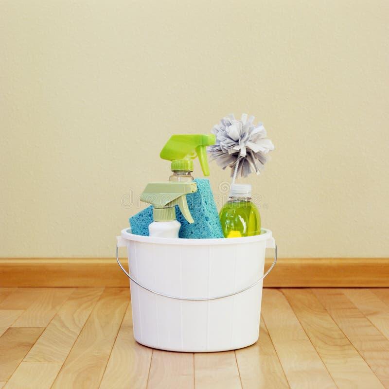 Secchio di plastica del secchio con i rifornimenti di prodotti sostenibili e ecologici di pulizia sul pavimento di legno pulito e fotografia stock libera da diritti