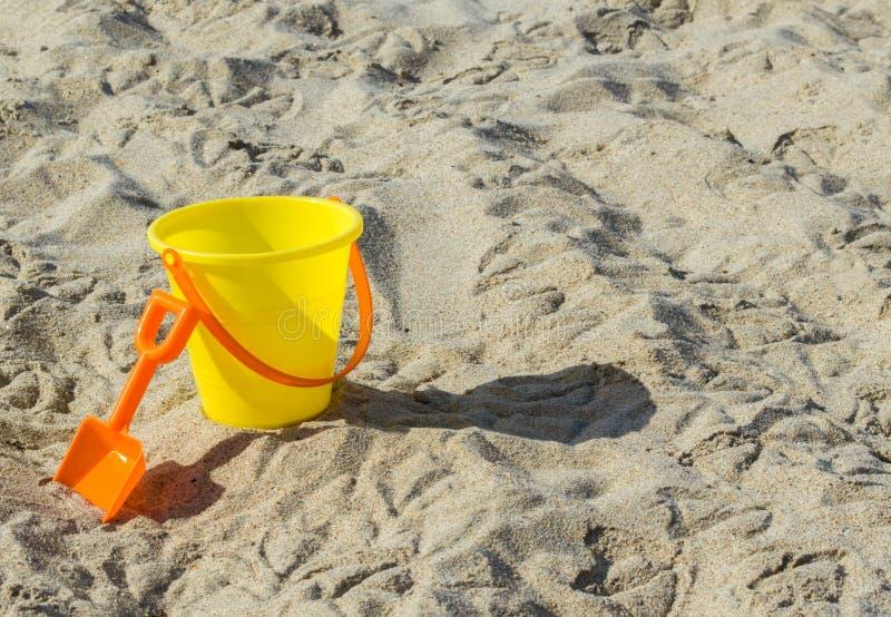 Secchio di plastica giallo della sabbia con la pala arancio ad una spiaggia sabbiosa immagini stock libere da diritti