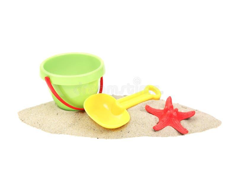 Secchio e showel di plastica sulla sabbia isolata fotografia stock libera da diritti