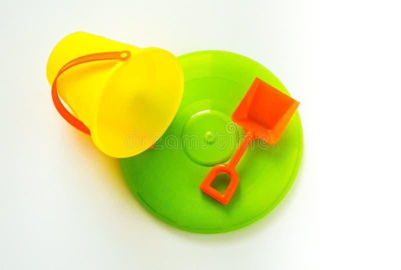 Secchio giallo luminoso e pala arancio con il frisbee verde isolati su bianco immagine stock libera da diritti