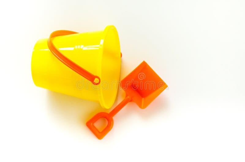 Secchio giallo luminoso e pala arancio isolati su bianco immagine stock libera da diritti