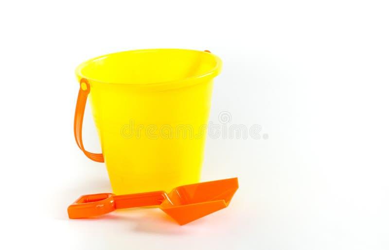 Secchio giallo luminoso e pala arancio isolati su bianco immagini stock