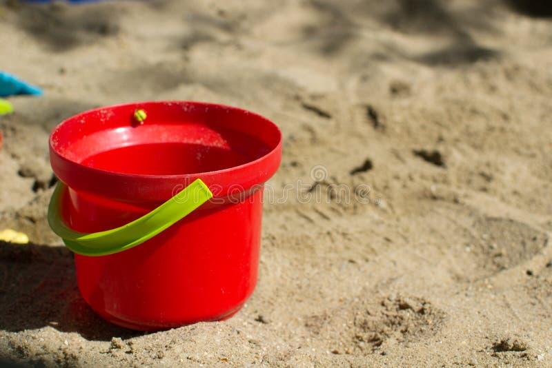 Secchio rosso del bambino con una maniglia verde nella fine della sabbiera su immagine stock libera da diritti
