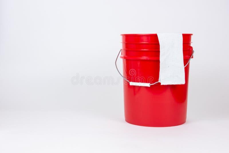 Secchio rosso isolato con il panno del lavaggio su fondo bianco fotografie stock libere da diritti