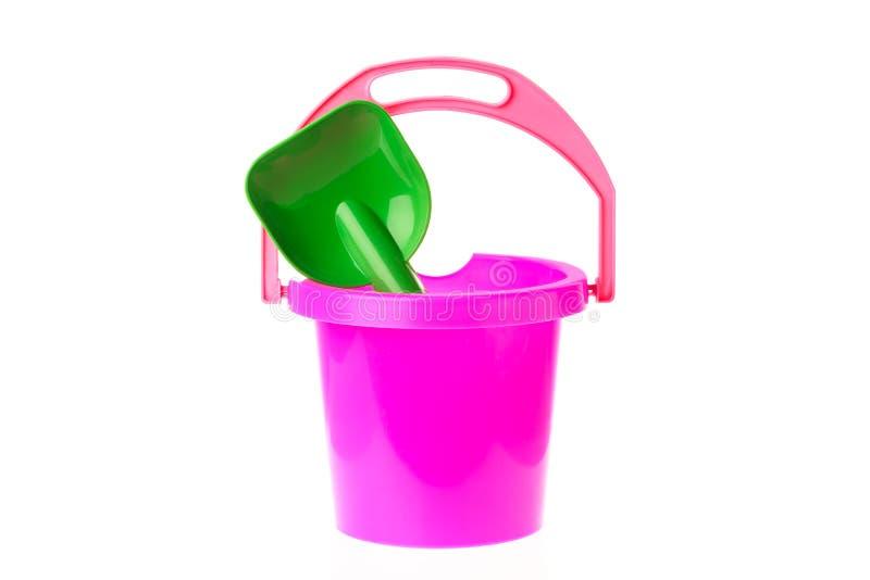 Secchio variopinto e pala del giocattolo isolati su fondo bianco Giocattoli per i bambini immagini stock libere da diritti