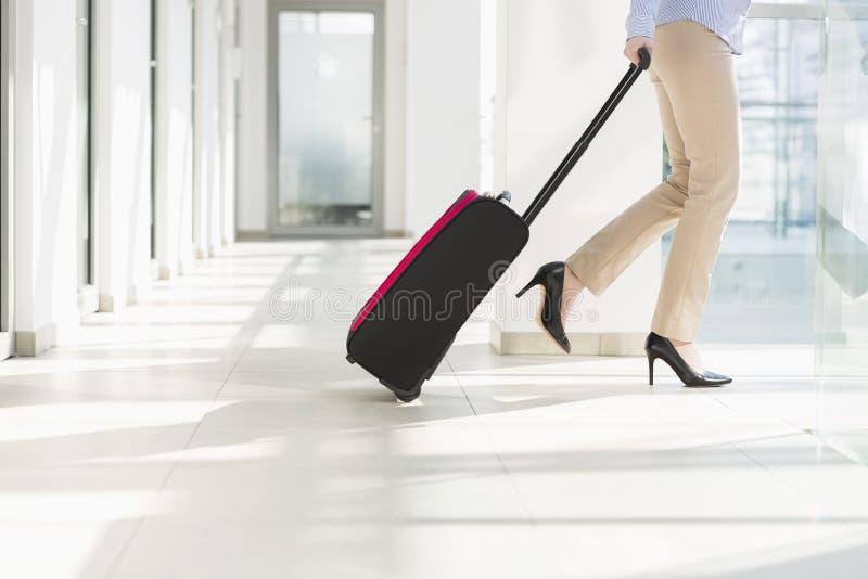 Sección baja de la empresaria con el equipaje que sale el aeropuerto fotos de archivo