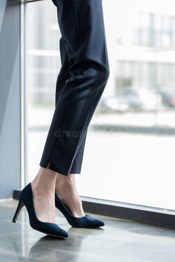 sección baja de la empresaria en la colocación de los zapatos de tacón alto imágenes de archivo libres de regalías