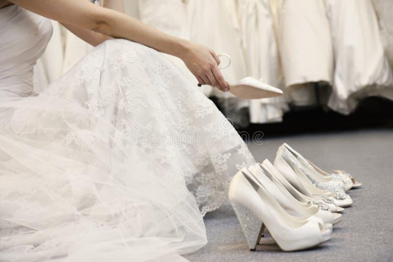 Sección baja de la mujer que se sienta con la variedad de calzado en boutique nupcial imagen de archivo libre de regalías