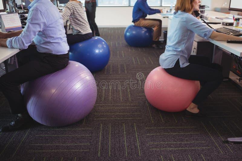 Sección baja de los hombres de negocios que se sientan en bolas del ejercicio mientras que trabaja en la oficina fotos de archivo