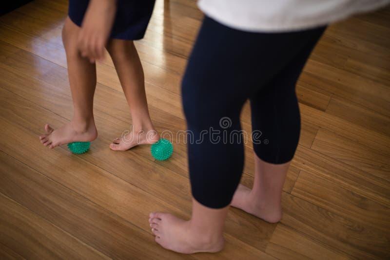 Sección baja del terapeuta de sexo femenino que detiene al muchacho que se coloca en bolas de la tensión fotografía de archivo