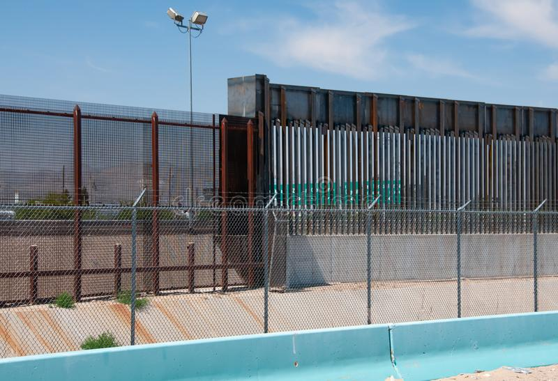 Sección de la pared de la frontera en El Paso, TX que muestra viejo estilo en izquierdo y nuevo en la derecha imagenes de archivo