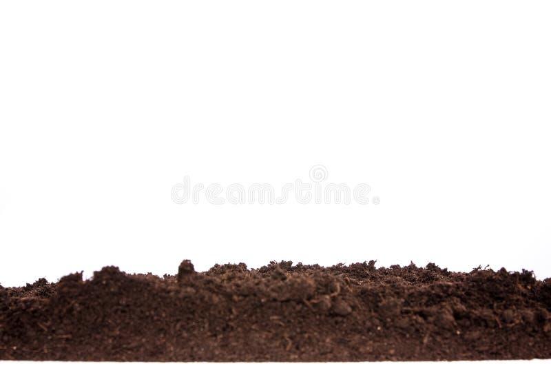 Sección del suelo o de la suciedad aislada en el fondo blanco fotografía de archivo