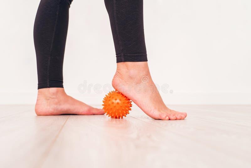 Secci?n baja de la muchacha que ejercita con la bola de la tensi?n en hospital bola del masaje bajo pie fotografía de archivo