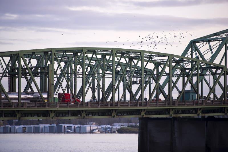 Seccione el puente del arco de la estructura con el camión y la multitud de pájaros foto de archivo
