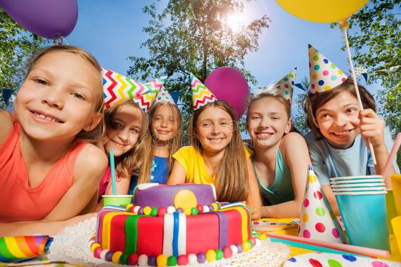Sechs glückliche Kinder in den Parteihüten um Geburtstagskuchen lizenzfreies stockbild