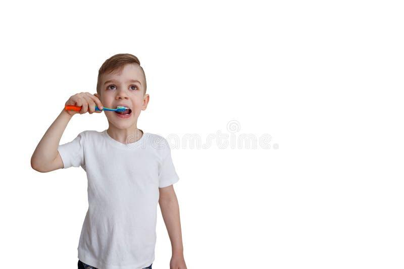 Sechs jährige Jungenbürsten seine Zähne Mundpflege-Konzept Lokalisiert auf weißem Hintergrund mit einem Kopienraum lizenzfreies stockbild
