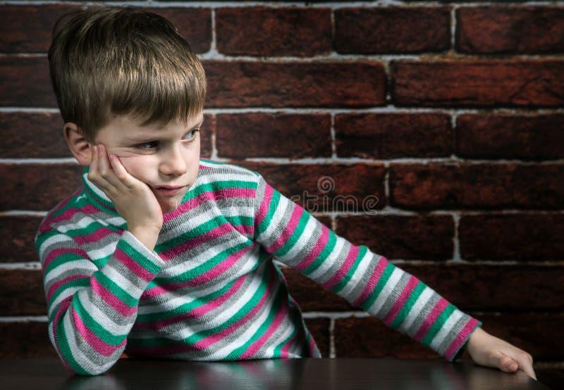 Sechs Jährigjunge mit einem durchdachten Ausdruck stockfoto