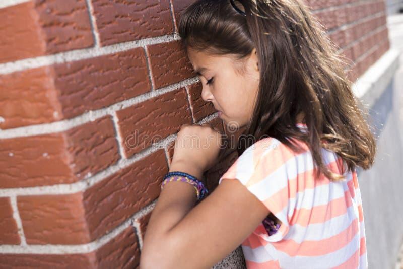 Sechs Jahre alte Schulmädchenschrei neben Backsteinmauer lizenzfreies stockbild