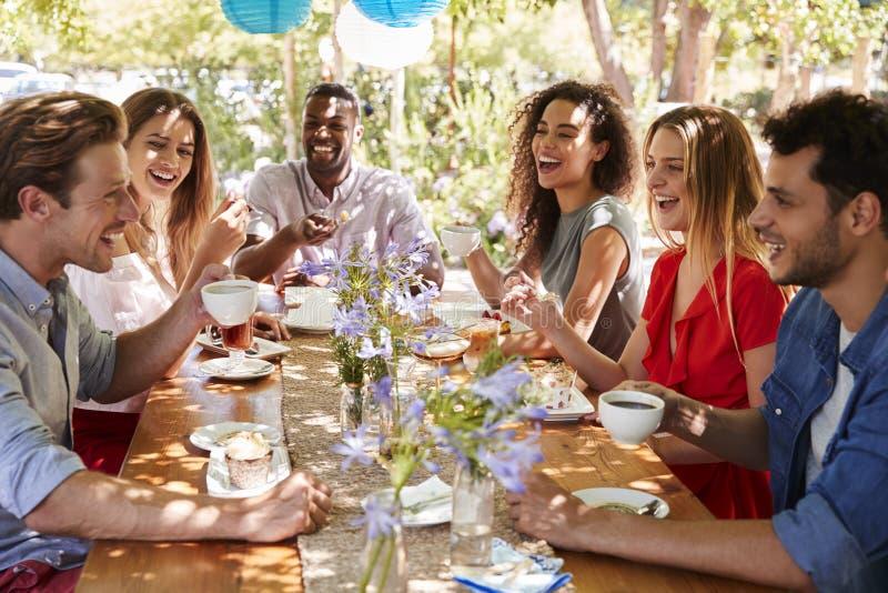 Sechs junge erwachsene Freunde, die Kaffee trinken, nachdem draußen speisen stockfotografie