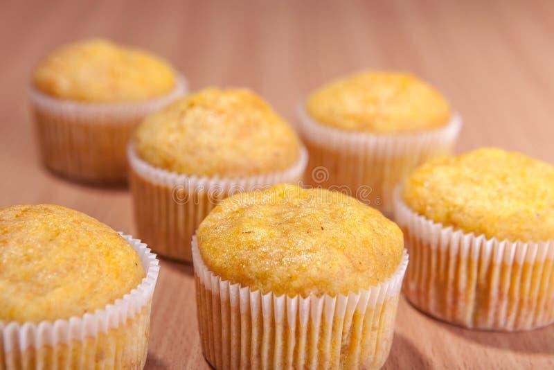 Sechs kleine Kuchen auf hölzerner Beschaffenheitstabelle lizenzfreie stockfotos
