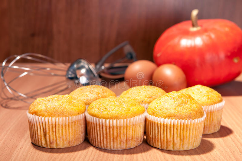Sechs kleine Kuchen, Kürbis und Backenküchengeschirr auf hölzerner Beschaffenheitstabelle lizenzfreie stockbilder