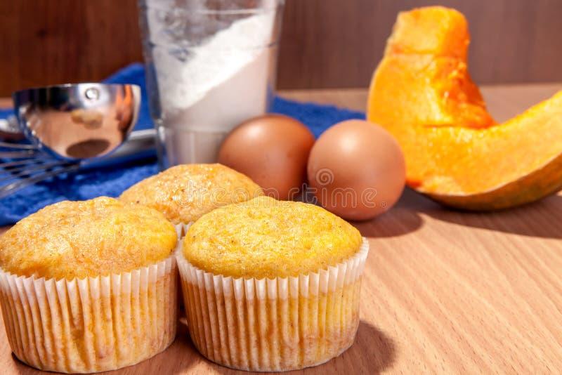 Sechs kleine Kuchen, Kürbis und Backenküchengeschirr auf hölzerner Beschaffenheitstabelle stockfotos
