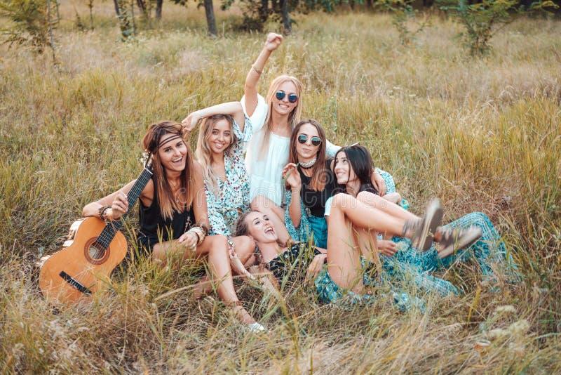 Sechs Mädchen in der Natur sitzen auf dem Gras stockbilder