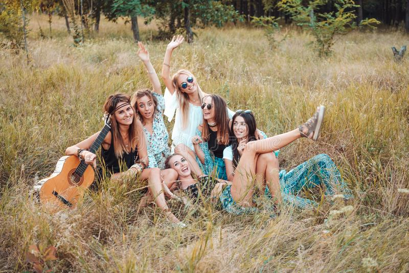 Sechs Mädchen in der Natur sitzen auf dem Gras stockfotografie