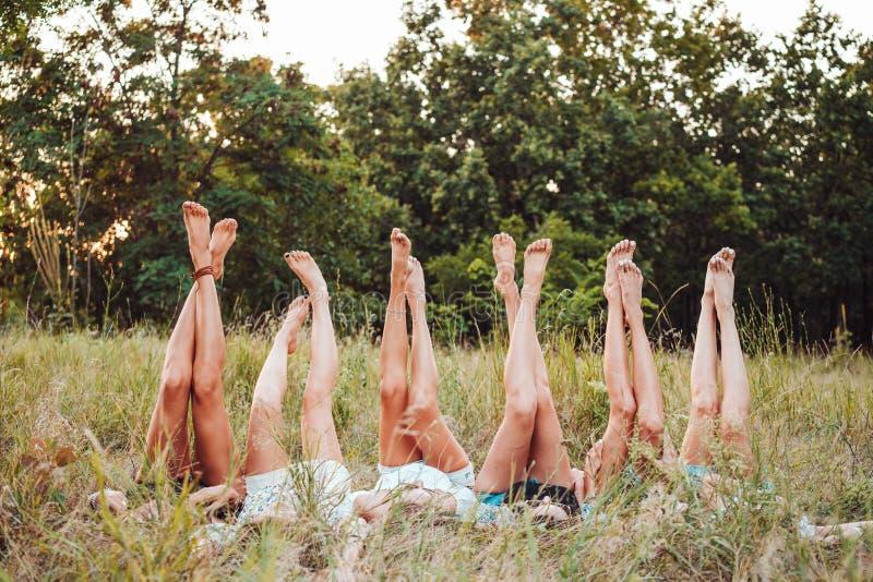 Sechs Mädchen liegen auf dem Gras und heben ihre Beine oben an lizenzfreies stockbild