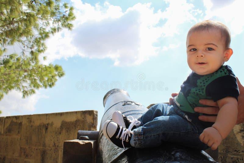 Sechs Monate alte Baby, die auf Kanon mithilfe von dady sitzen lizenzfreie stockfotografie