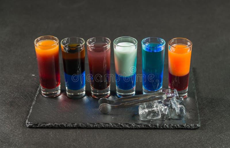 Sechs verschiedene farbige Schussgetränke, ausgerichtet auf einem schwarzen Steinwinkel des leistungshebels lizenzfreie stockfotografie