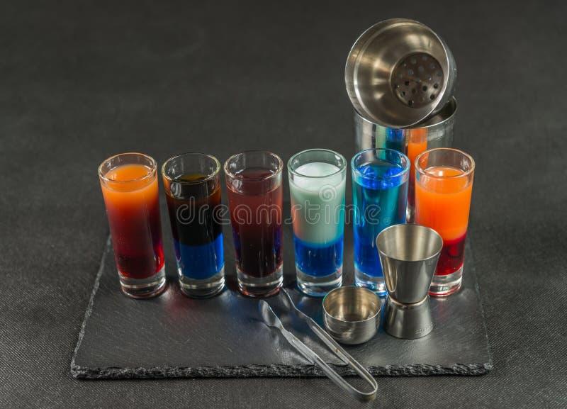 Sechs verschiedene farbige Schussgetränke, ausgerichtet auf einem schwarzen Steinwinkel des leistungshebels stockbild