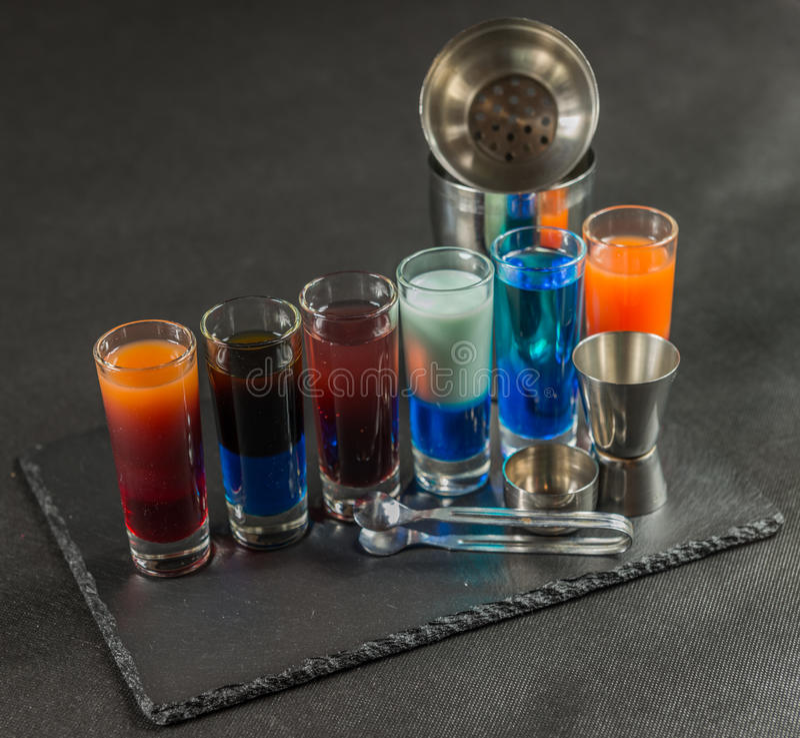 Sechs verschiedene farbige Schussgetränke, ausgerichtet auf einem schwarzen Steinwinkel des leistungshebels lizenzfreie stockfotos