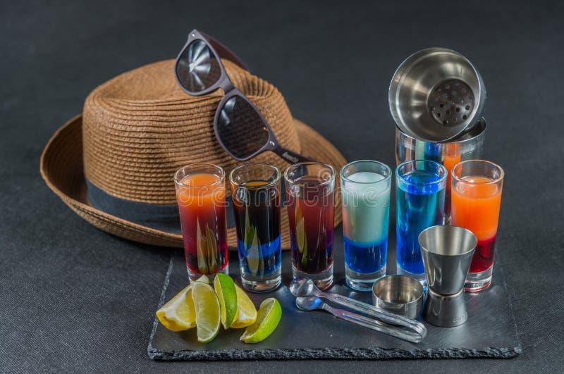 Sechs verschiedene farbige Schussgetränke, ausgerichtet auf einem schwarzen Steinwinkel des leistungshebels stockfotos