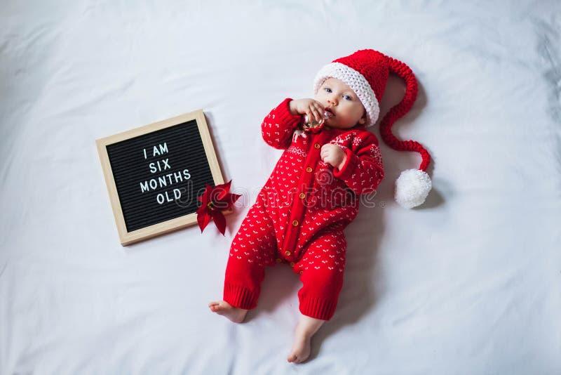 6 Sechsesechs Monate altes Baby auf weißem Untergrund mit Santa Kostüme Flachlagenzusammensetzung stockbilder