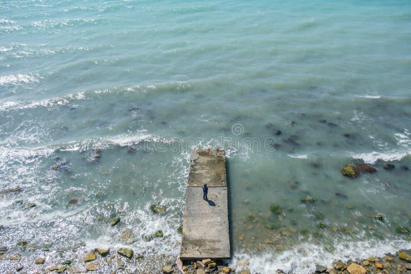 Sechsjähriger Junge steht auf einem Pier in Meer während eines Sturms mit Wellen Sonniger Tag des Frühlinges in Meer lizenzfreie stockfotografie