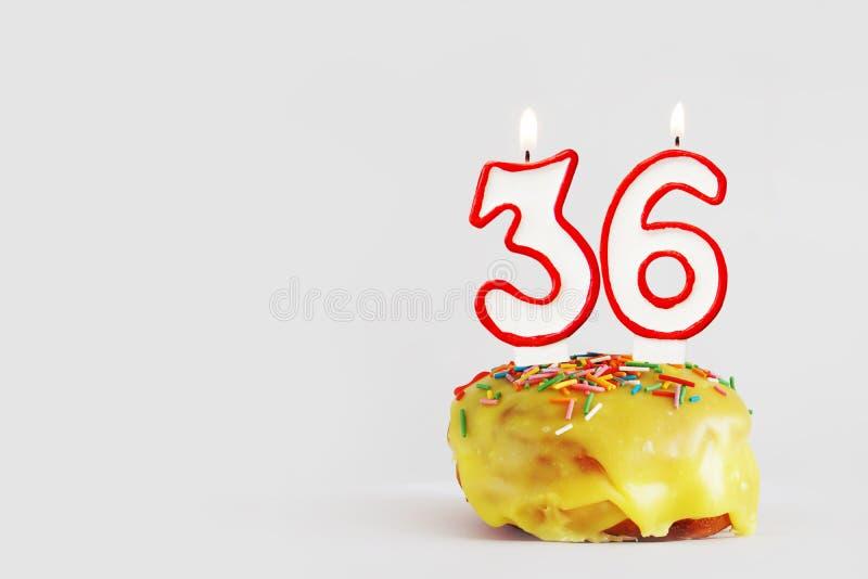 Sechsunddreißig Jahre Jahrestag Geburtstagskleiner kuchen mit weißen brennenden Kerzen mit roter Grenze in Form von Nr. sechsundd lizenzfreie stockfotos