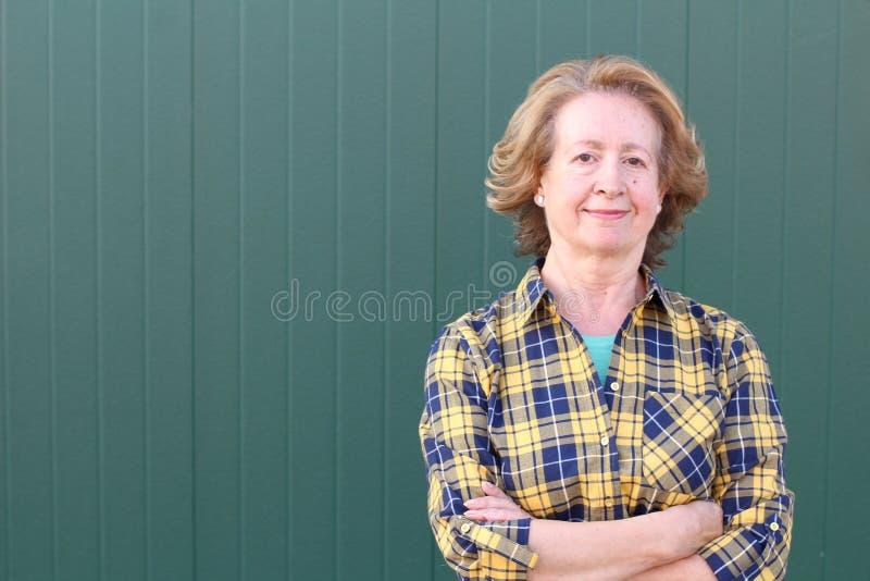 Sechzig Jahre alte Frau mit den Armen gekreuzt lizenzfreie stockfotografie