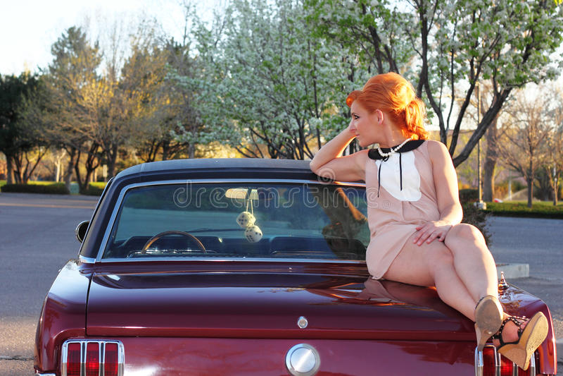 Sechziger-Frau auf Muskel-Auto lizenzfreie stockfotos