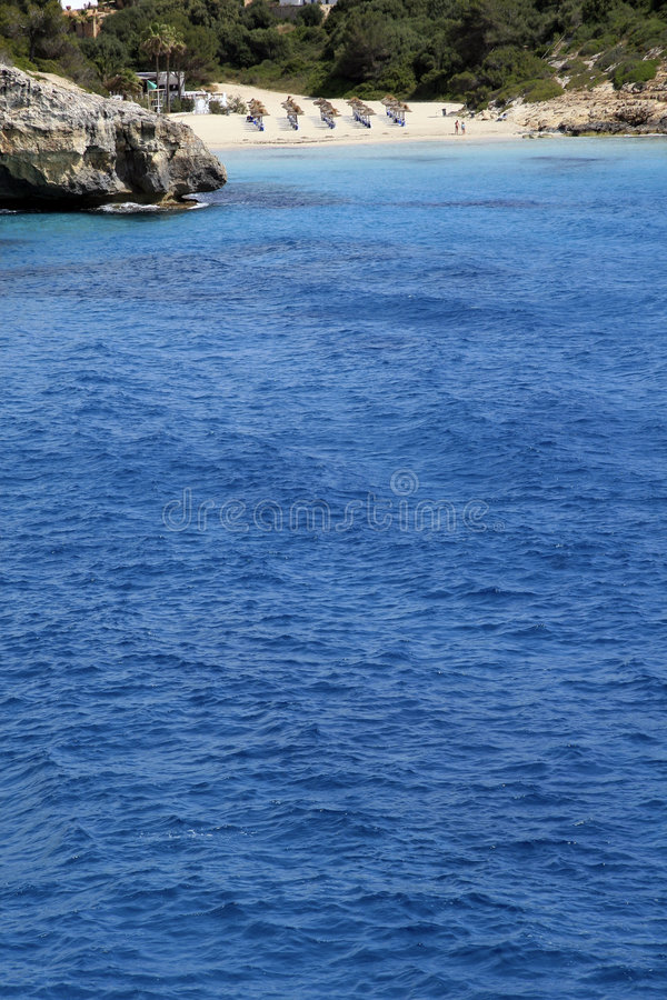 Secluded beach on Majorca. A view of the beautiful blue water and a secluded, romantic beach in the distance on the Spanish island of Majorca royalty free stock photography