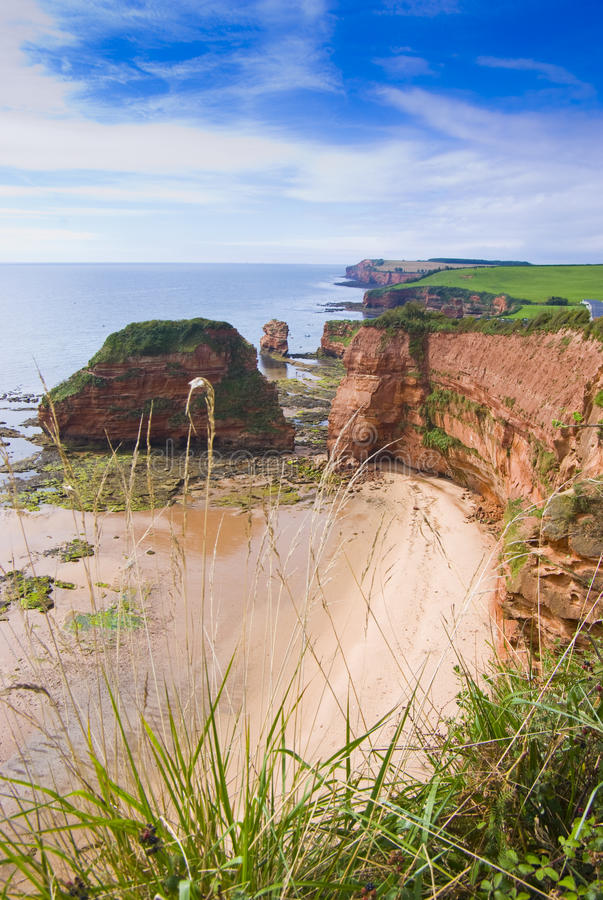 Secluded beach by ocean. Aerial view of secluded beach by ocean, Ladram Cove, Devon, England stock photos