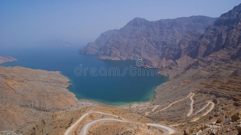Secluded Beach in the Oman Mountains. Overlooking a winding mountain road down to a secluded beach at the most Northern point of Oman royalty free stock photos