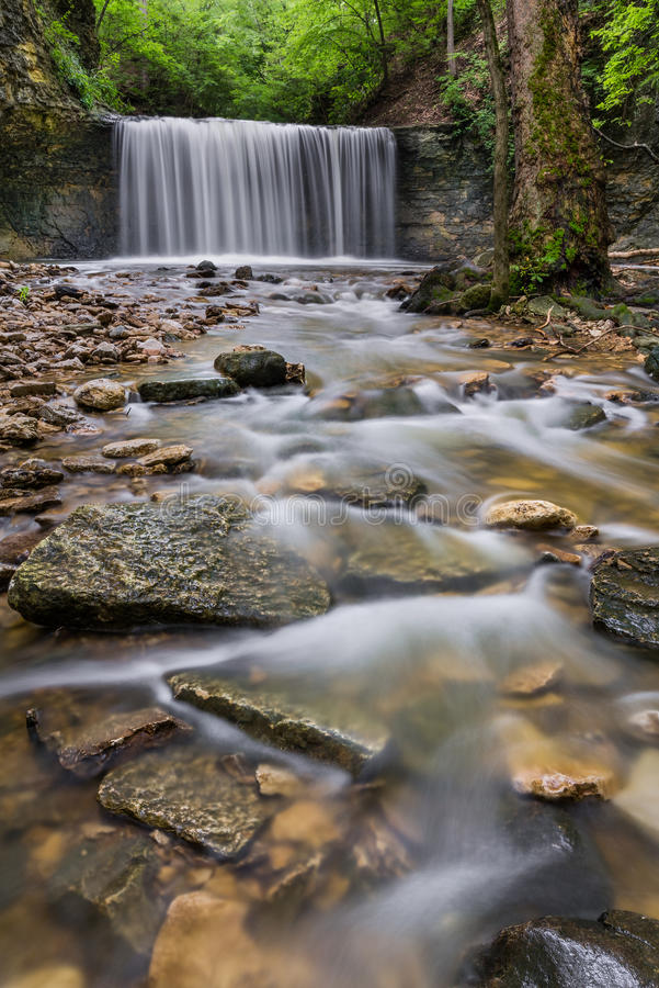 Secluded Ohio Waterfall. The lower waterfall at Indian Run Falls flows in a secluded area in the middle of an urban setting near Columbus, Ohio stock image