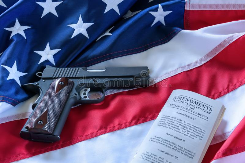 The second amendment and gun control in the US, concept. A handgun and the american constitution on the USA flag. royalty free stock image