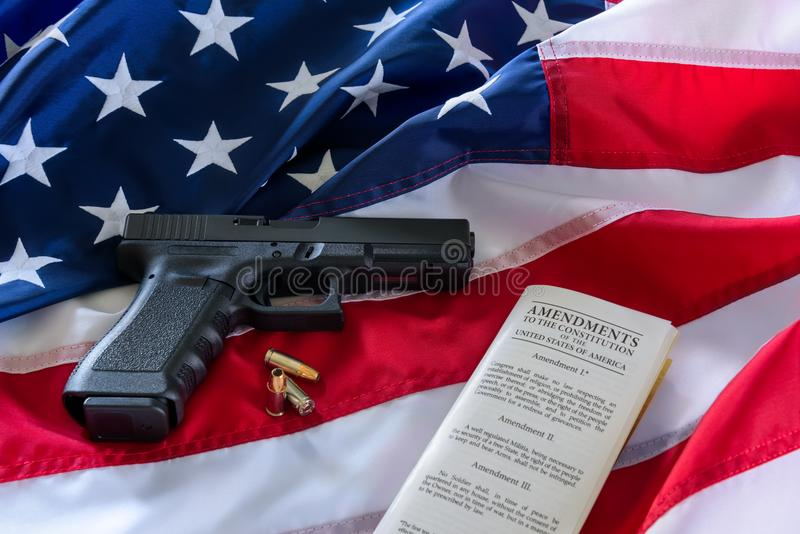 The second amendment and gun control in the US, concept. Handgun, bullets, and the american constitution on the USA flag.  stock photo