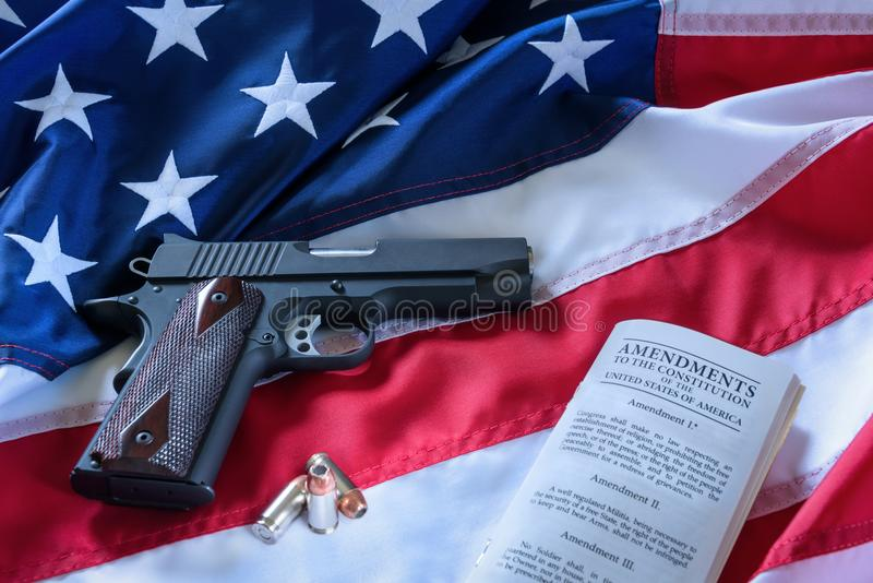 The second amendment and gun control in the US, concept. A handgun, bullets, and the american constitution on the USA flag. The second amendment and gun control stock photo