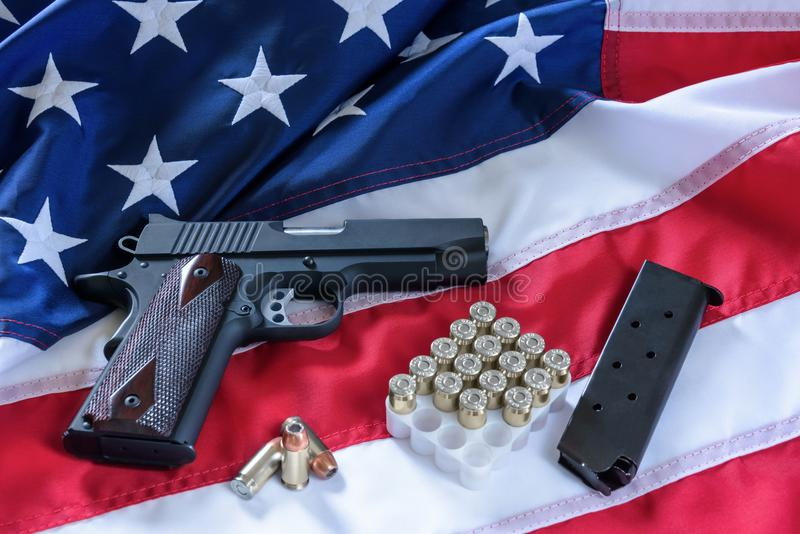 The second amendment and gun control in the US, concept. A handgun, a magazine, bullets, and the american constitution on the USA stock photos