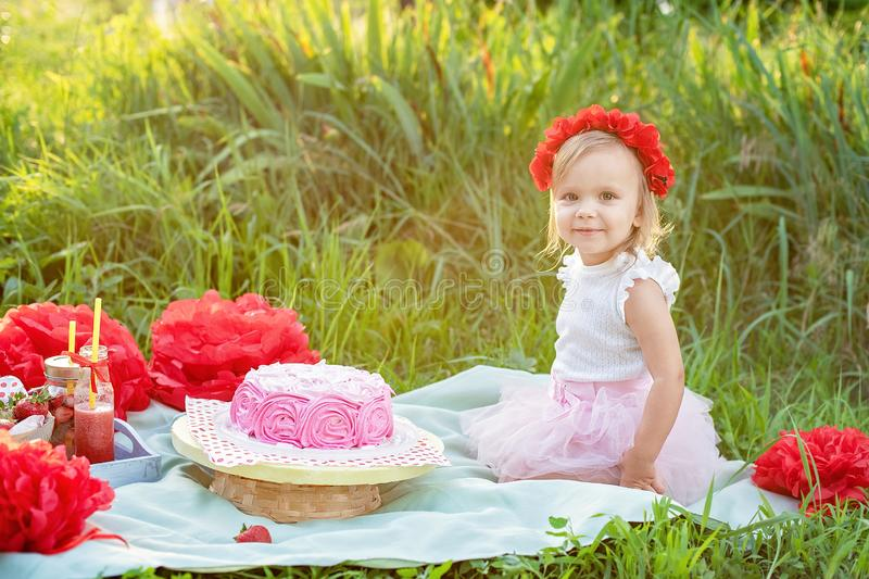 second birthday of little girl. Two years old girl sitting near celebration decorations and eating her birthday cake. Cake Smash stock photography